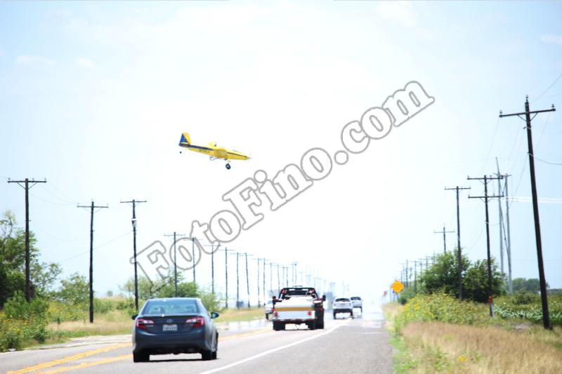 Crop Duster Flying Over Road - FotoFino.com